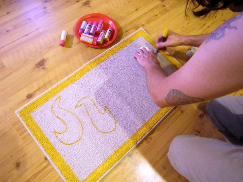 Painting embroidery pattern onto doormat.