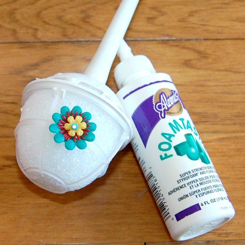 Attach plastic flowers to foam bouquet form with foam glue.
