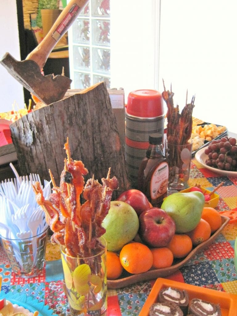 food table with a wood log and axe centerpiece