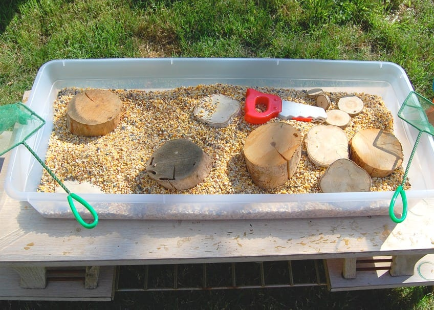 Sensory bin full of bird seed wood rounds and a toy saw