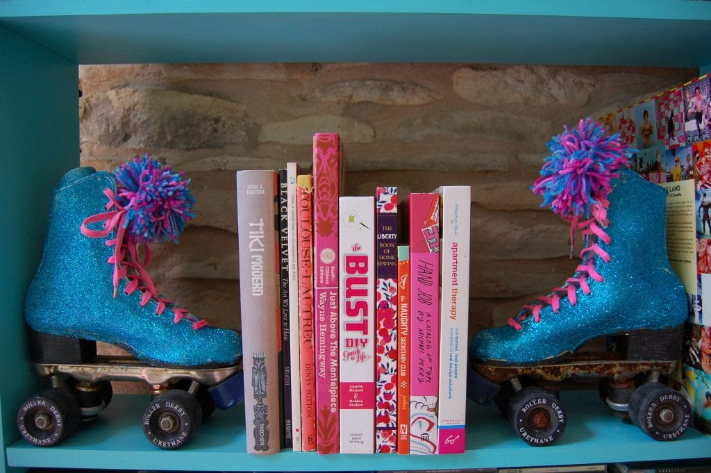Bookends made from a pair of vintage glittered roller-skates on a shelf.