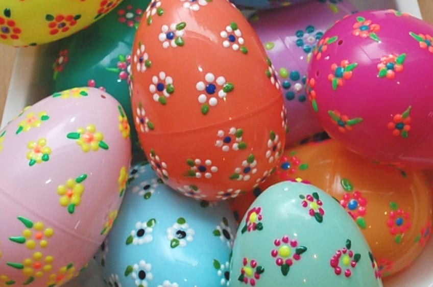 Bowl of colorful plastic Easter eggs decorated with flowers.