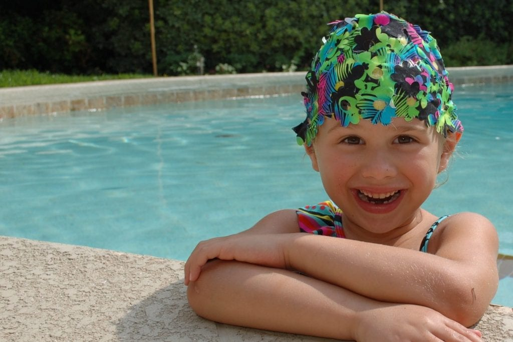 Girl in swim cap covered with flowers in the pool.
