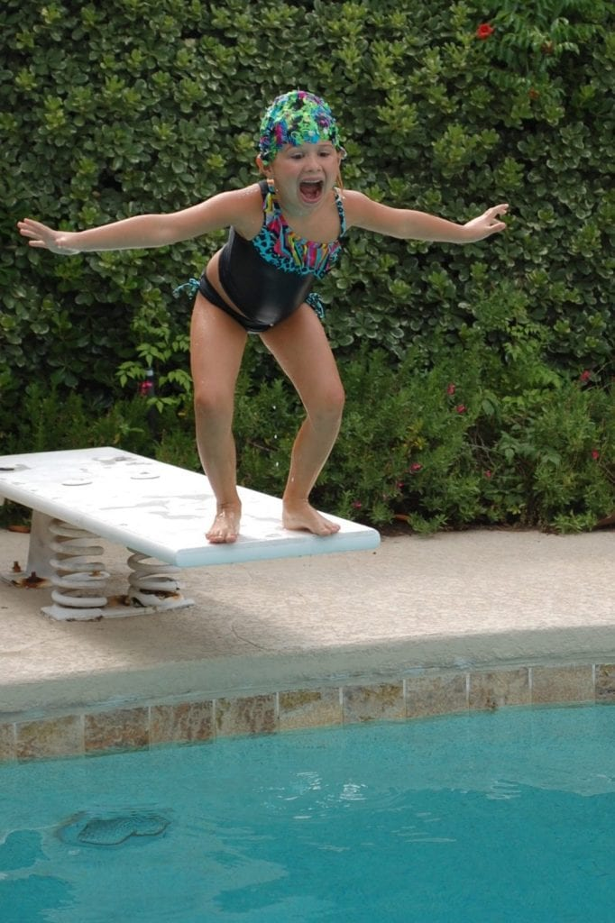 Girl in DIY swim cap jumping into pool.