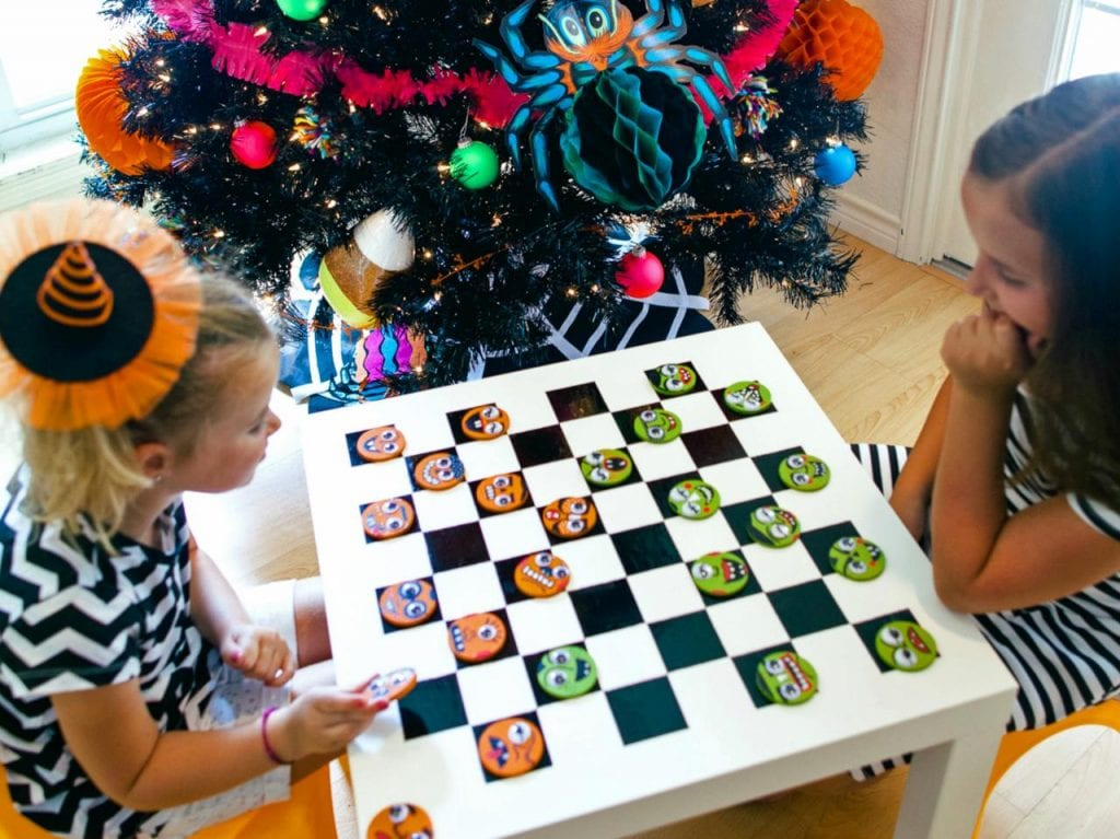 Kids playing checkers on an Ikea table with Halloween decorations