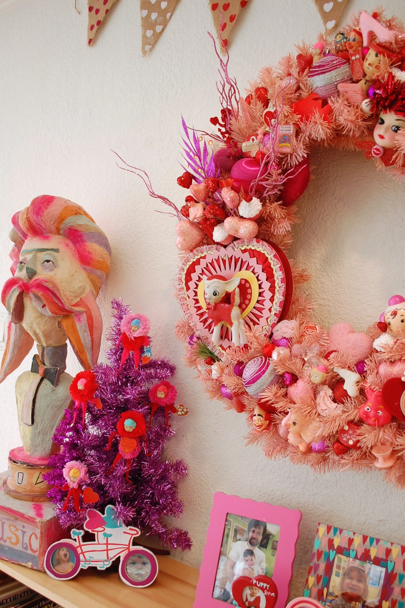 Pink Valentine's Day wreath covered in kitschy toys and trinkets by Jennifer Perkins