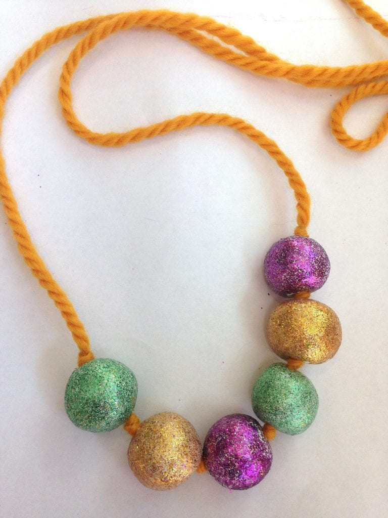 Kids Mardi Gras necklace with clay beads.