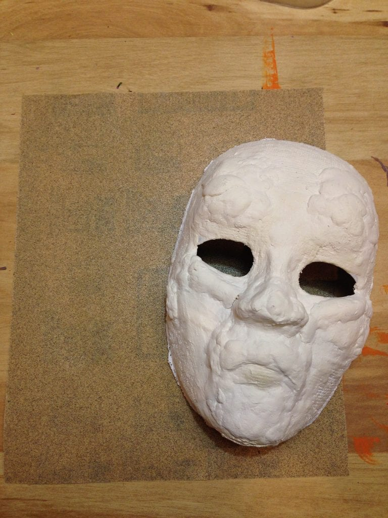 Sand the rough edges of your Halloween mask.
