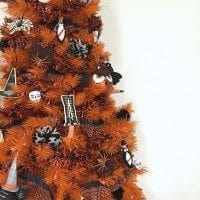 How to decorate an orange Halloween tree with DIY spider ornaments.
