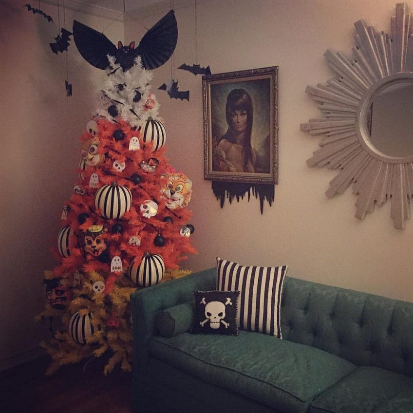 Halloween tree at night next to a mid-century green couch