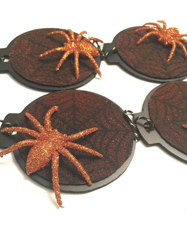 Glittered spiders on stenciled black Halloween tree web ornaments