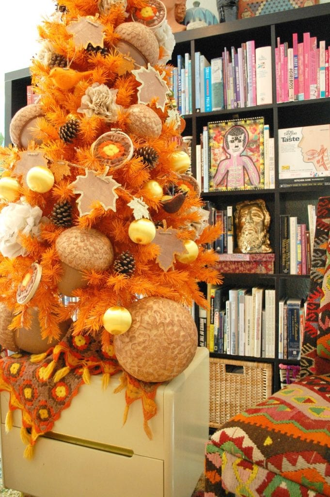 Decorating an orange Christmas tree for fall with DIY afghan ornaments by Jennifer Perkins