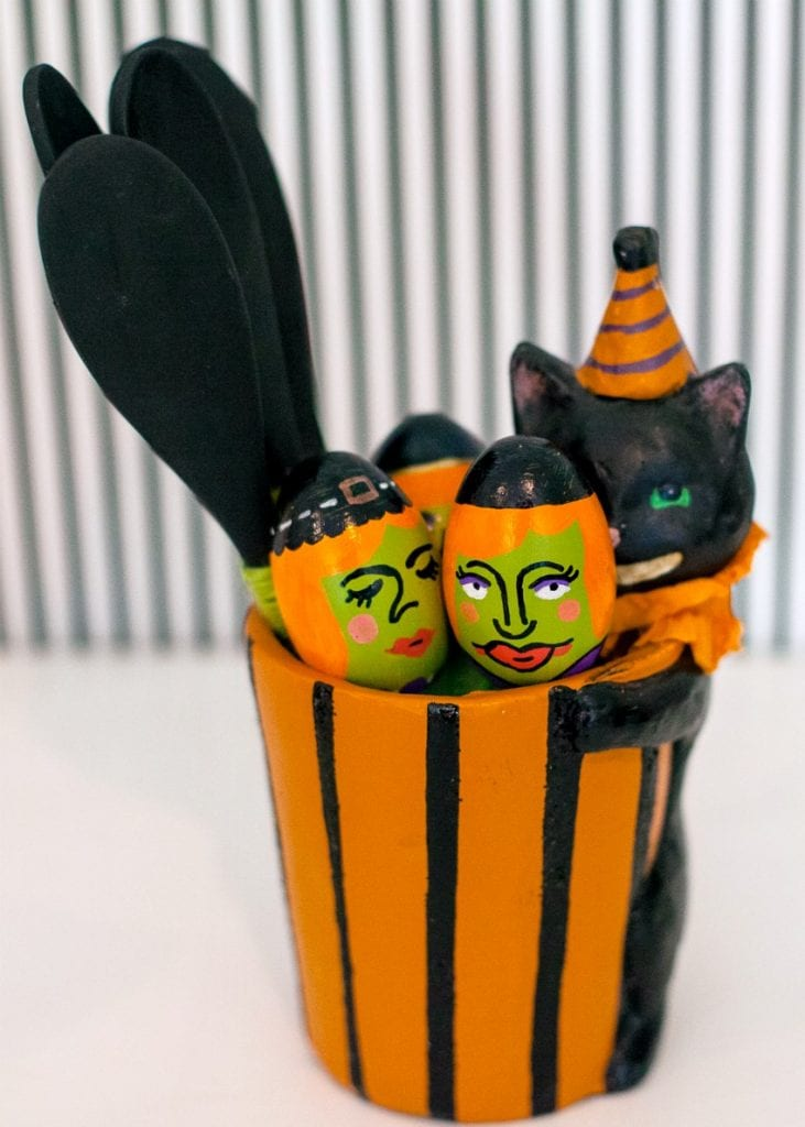 Black cat Halloween container holding painted eggs and spoons