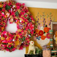 A hot pink wreath covered in yarn pompoms.
