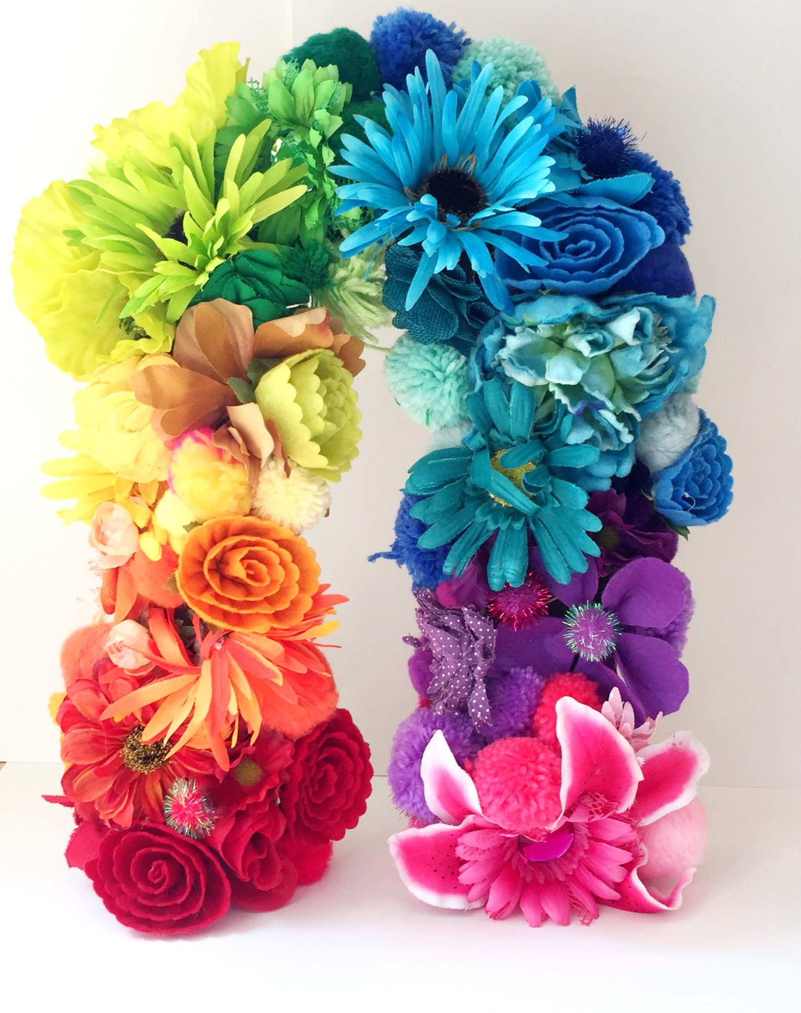 Rainbow made of faux flowers and pompoms by Jennifer Perkins