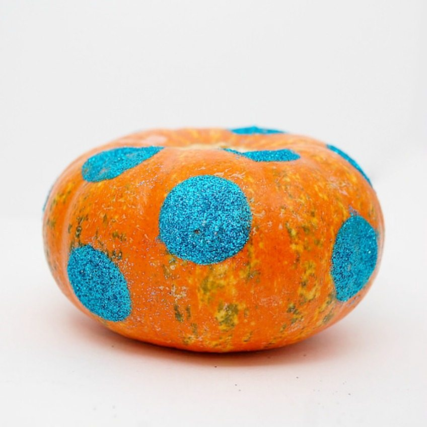 Adding teal glitter polka-dots to a pumpkin for Halloween by Jennifer Perkins