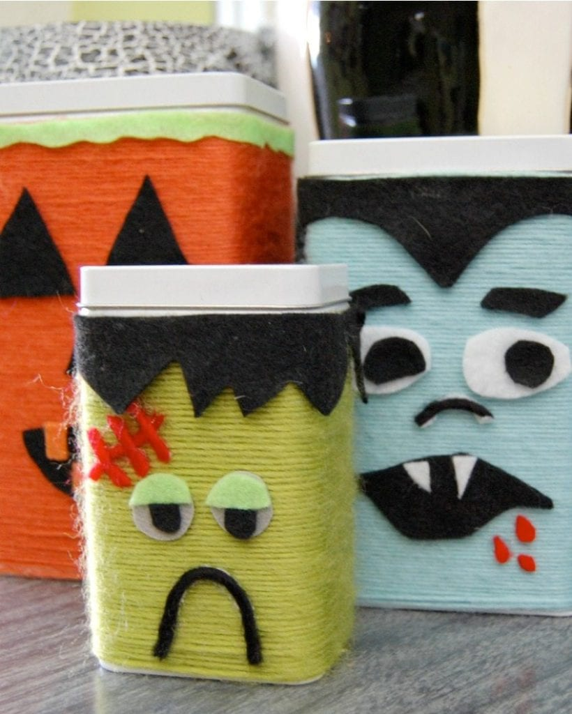Canisters wrapped in yarn to look like monsters