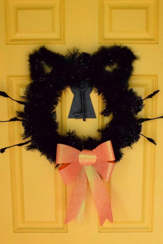 Black cat wreath on a yellow door