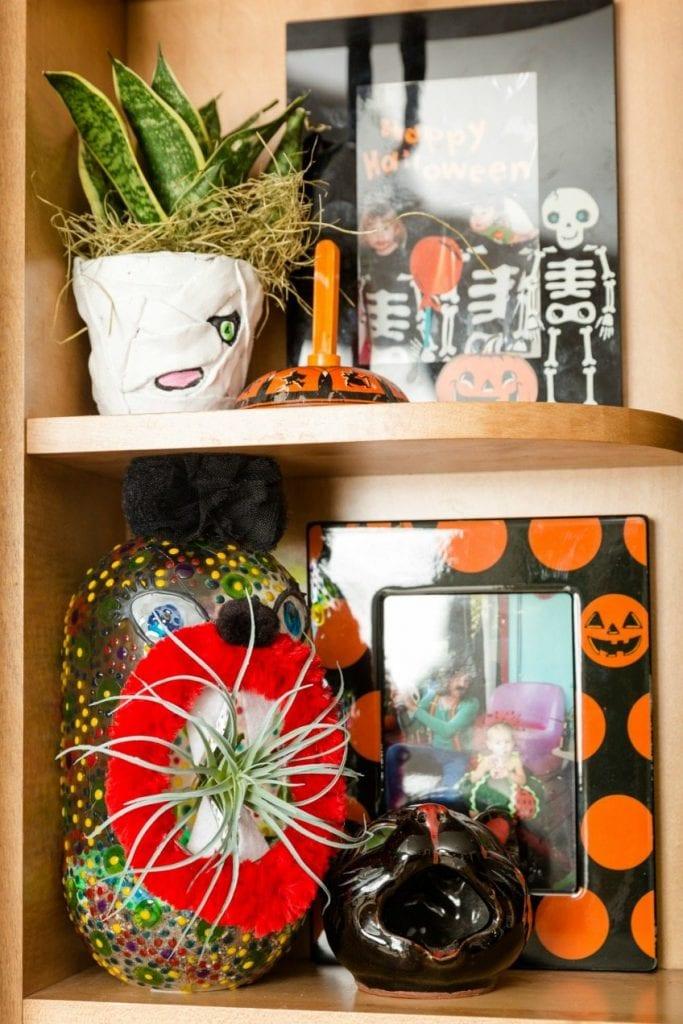 Shelf full of DIY Halloween planters by Jennifer Perkins