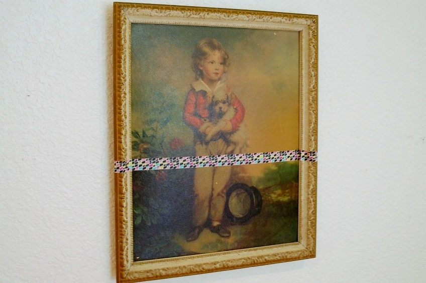 Apply strip of tape to thrift store art for paint dipped look