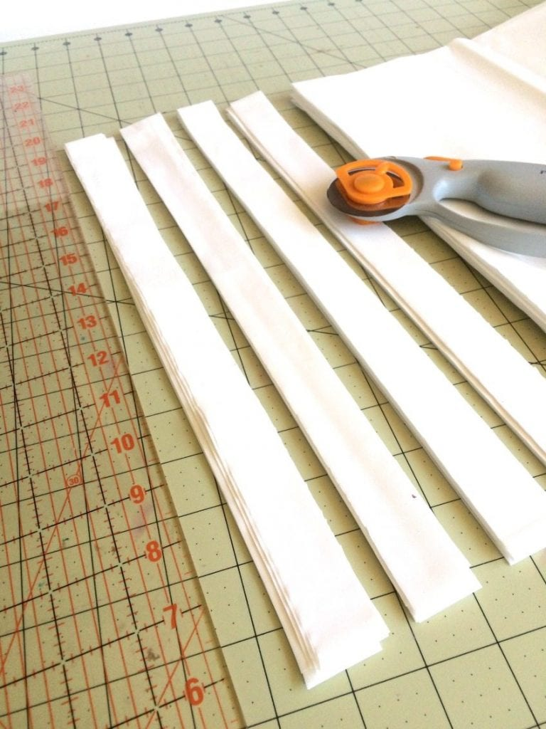 Cutting plastic table cloths for a fireplace screen.