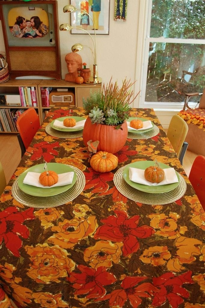 Table set for Thanksgiving with green plates and pumpkins