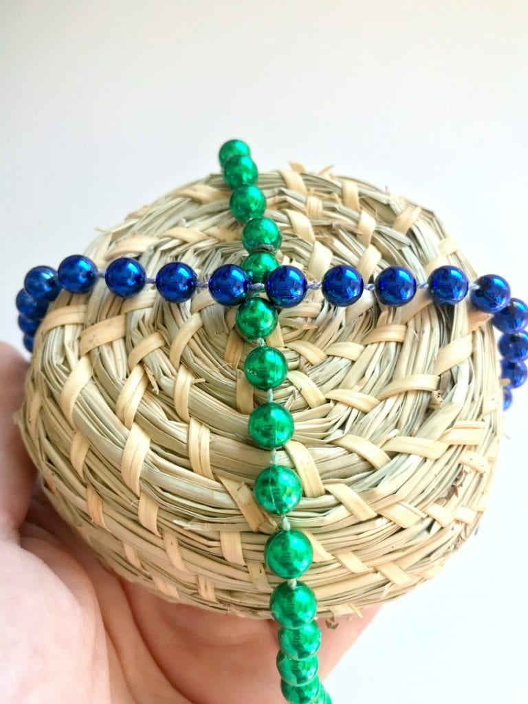 Criss cross the Mardi Gras beads over the bottom of the basket with hot glue to act as hangers.