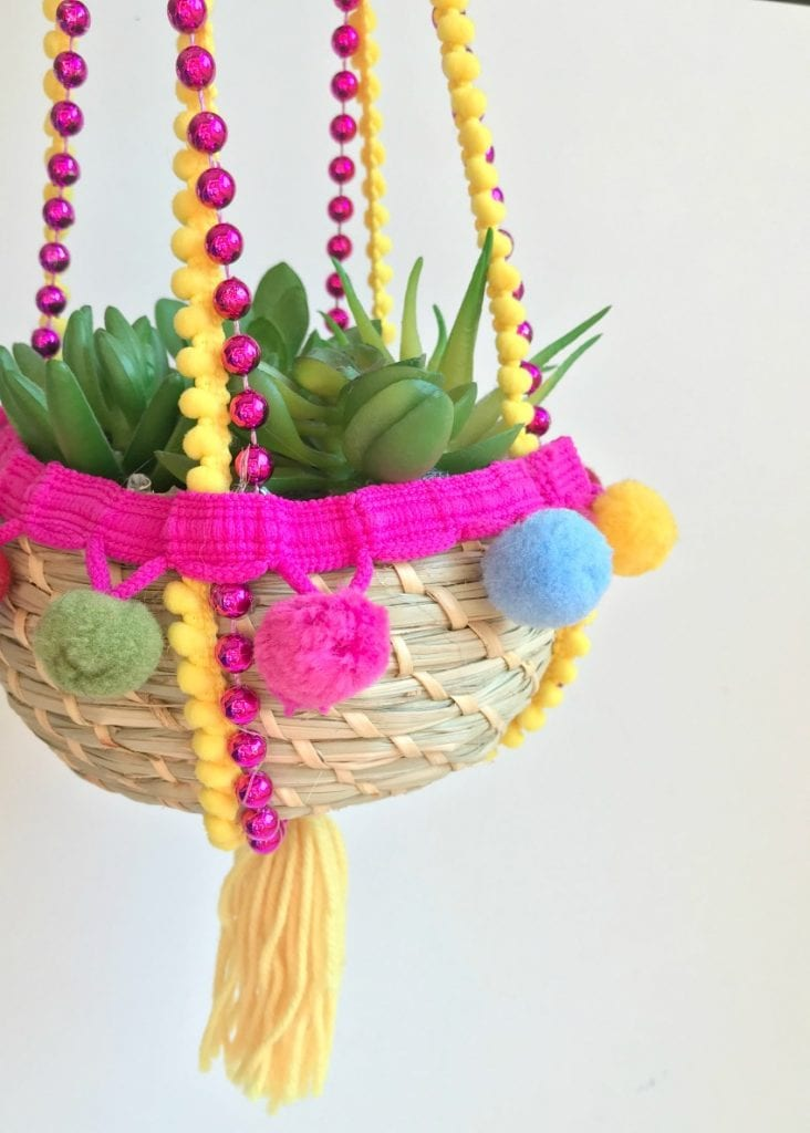 DIY hanging planter made with recycled Mardi Gras beads, pompom fringe and a tassel by Jennifer Perkins