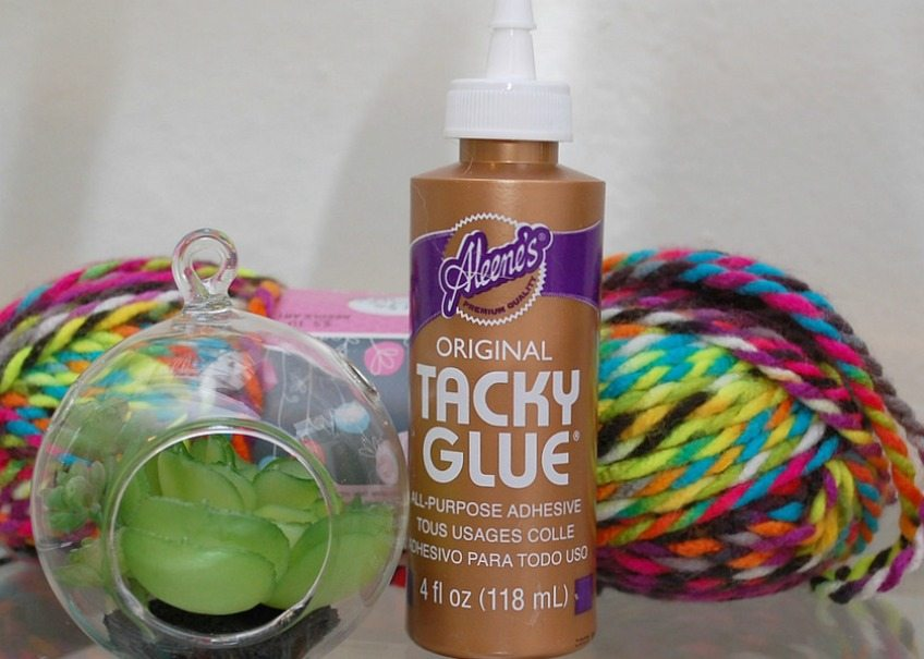 All the craft supplies you need for creating a yarn wrapped hanging planter.