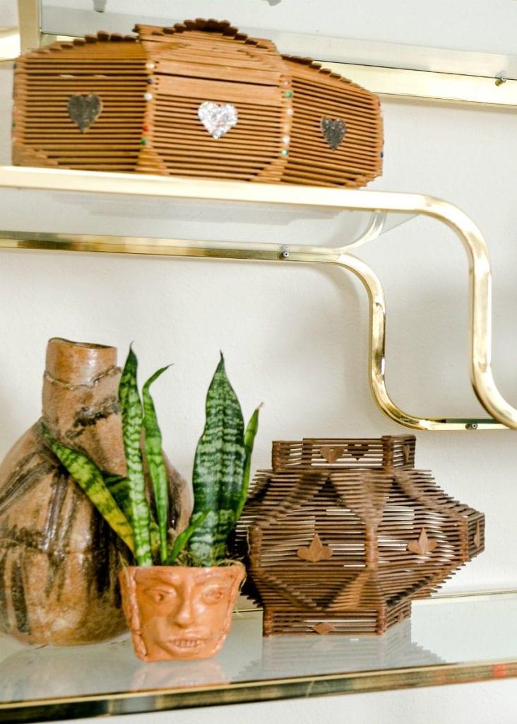 Bohemian style etagere with display of vintage tramp art. - Jennifer Perkins