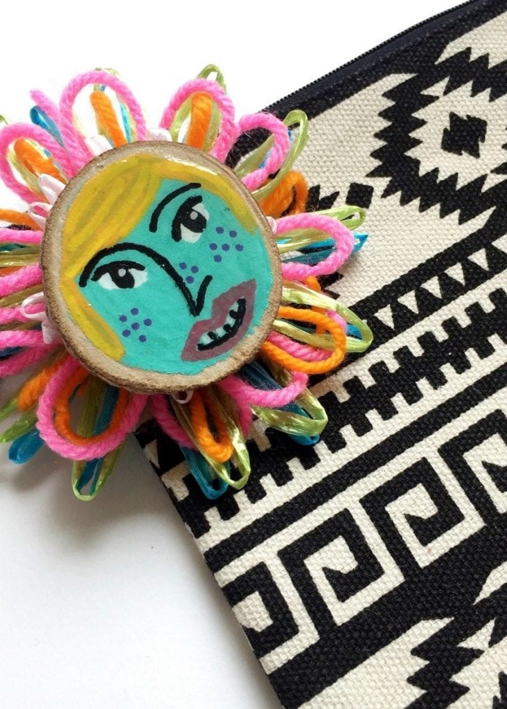 Yarn and raffia flower with painted wood disc.