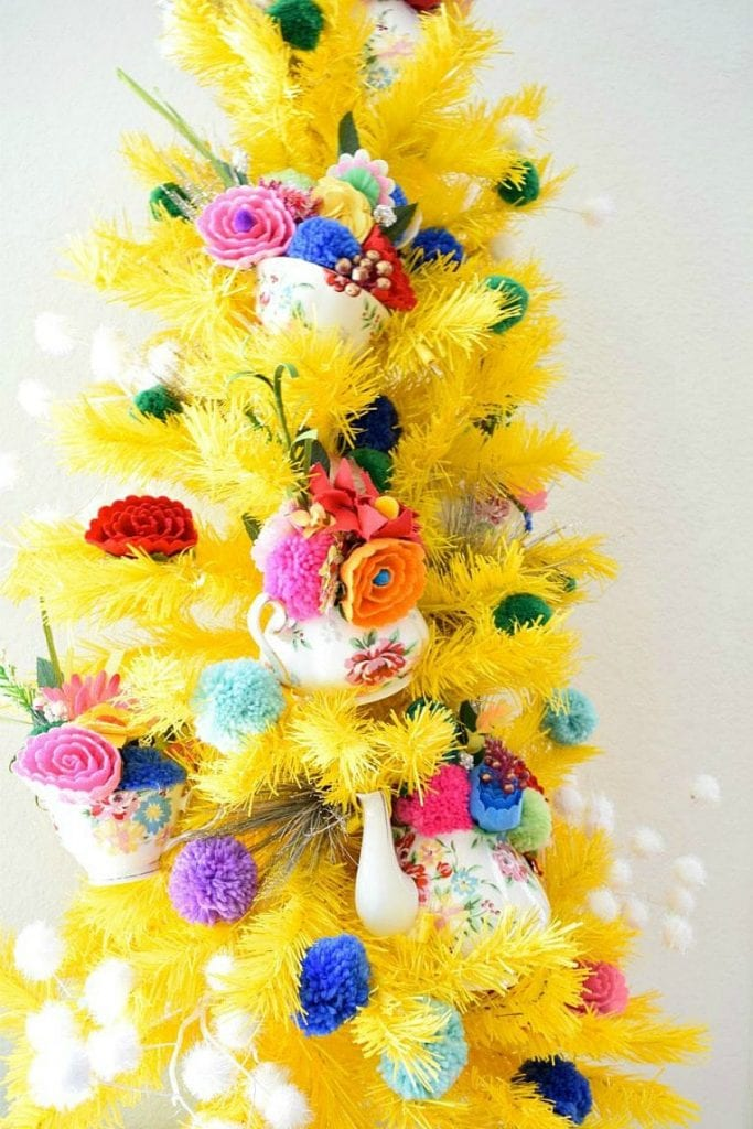 Yellow Christmas tree decorated for Mother's Day with flowers and tea pots by Jennifer Perkins