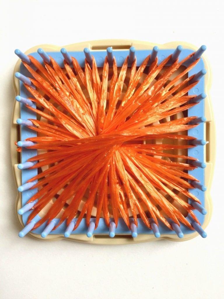 Stringing plastic straw raffia onto a flower loom.