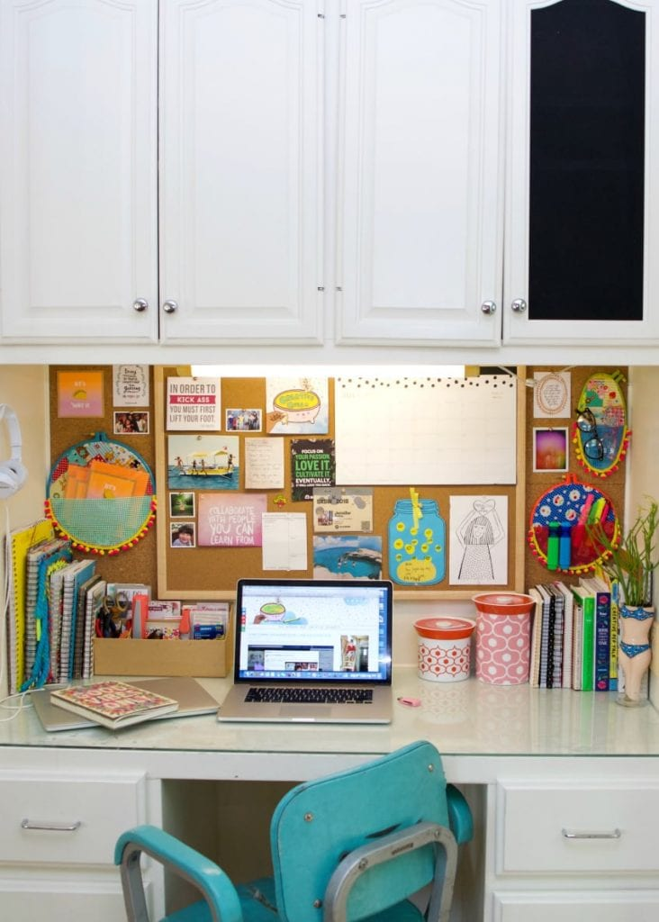 Desk with vision board and embroidery hoop wall pockets.