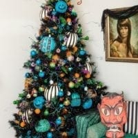 Black Halloween tree in a corner with a green couch and teal pumpkins