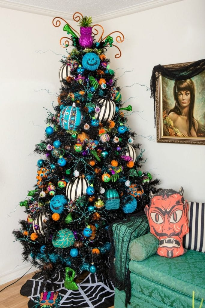 Black Christmas tree decorated for Halloween with DIY teal pumpkins.