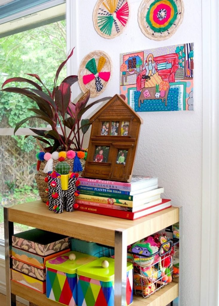 Styled shelf full of books and boho planters.