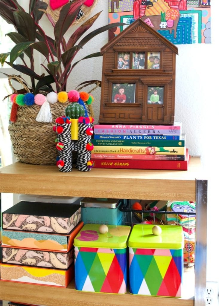 Colorful planters with pompoms on a book shelf.