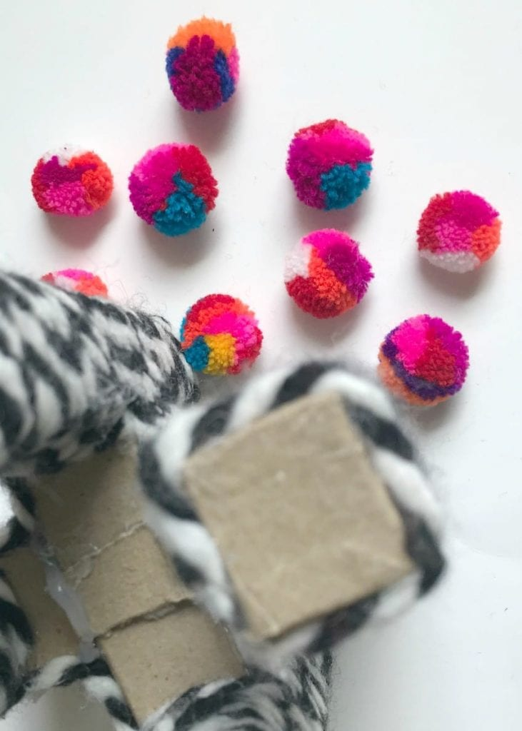 Cover the tops of the cardboard arms with colorful pompoms using hot glue.