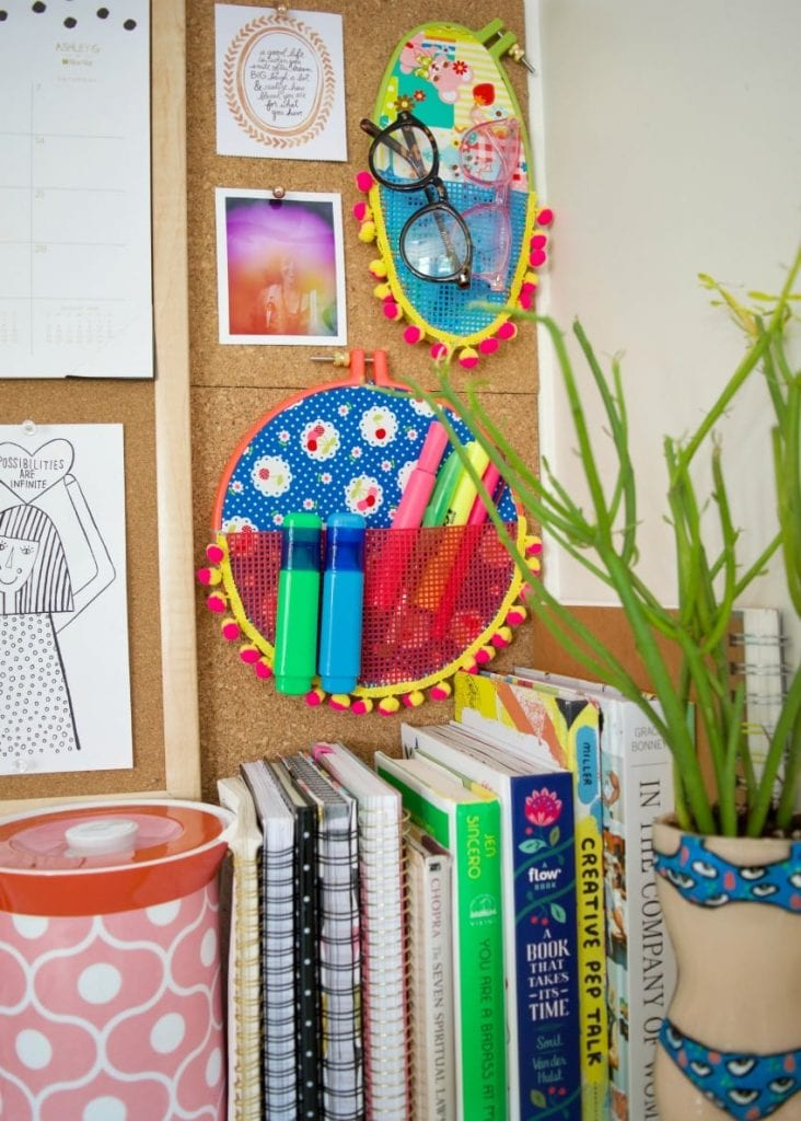 Wall pockets full of highlighters made from embroidery hoops and plastic canvas.