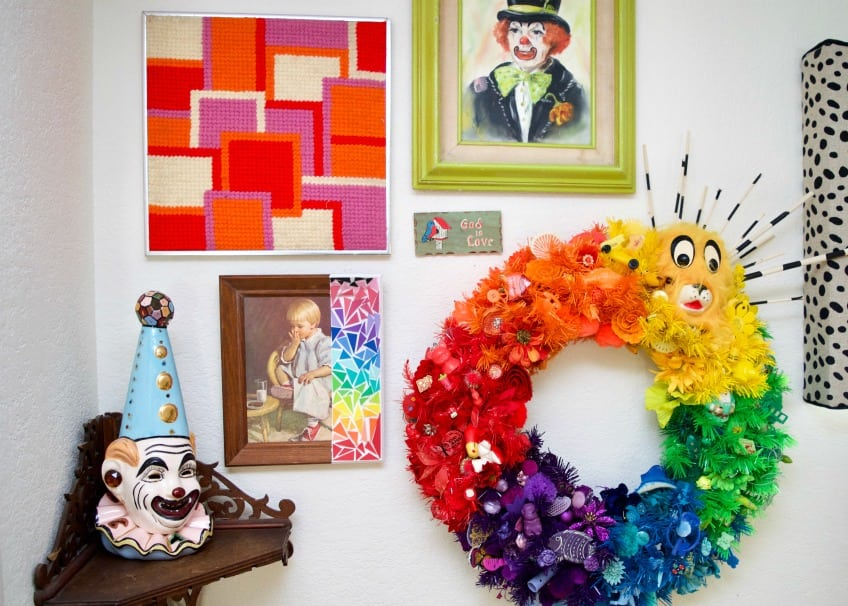 Eclectic gallery wall full of clown art, rainbows and wreaths.