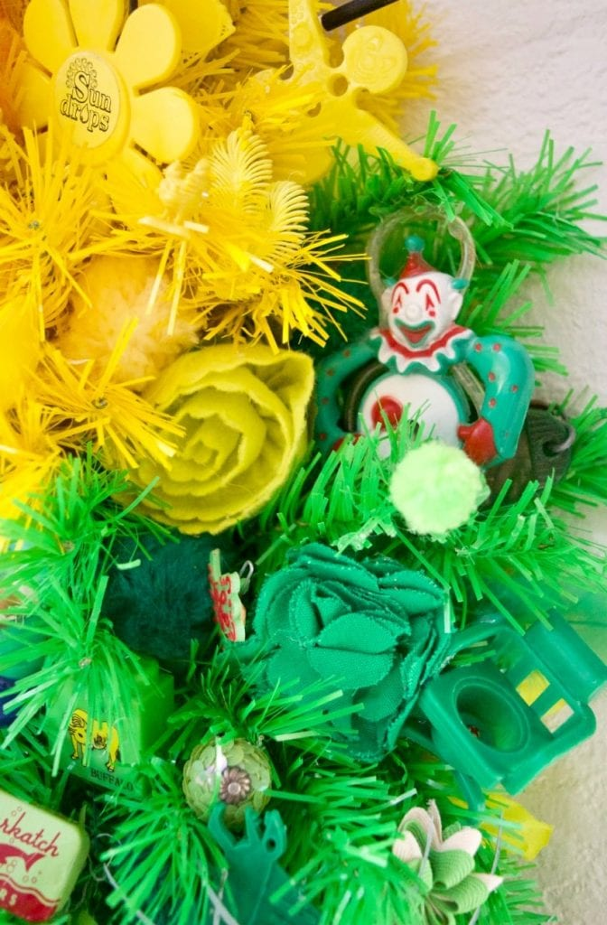 Small green vintage clown straw on an artificial wreath.