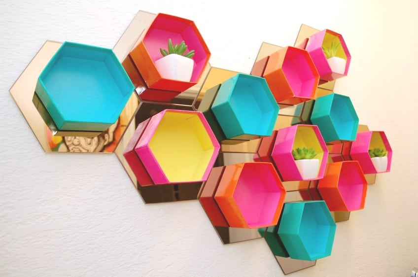 How to make a wall of DIY hexagon shelves using Ikea mirrors and colorful gift boxes.