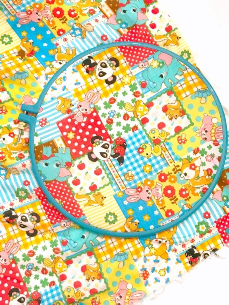 Japanese children's fabric with panda bears stretched in an embroidery hoop.
