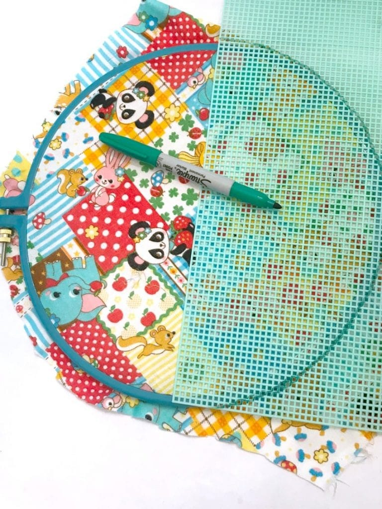 Measuring plastic canvas on top of embroidery hoop and marking where to cut with marker.