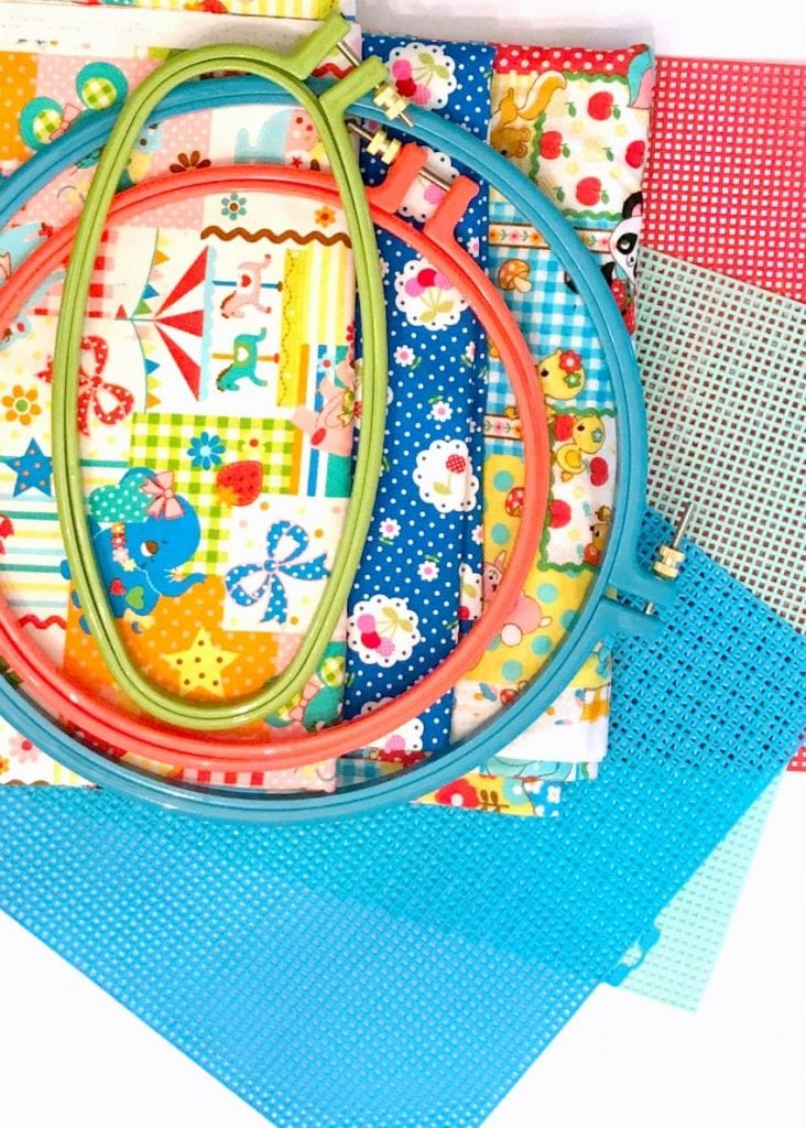 craft supplies including plastic embroidery hoops, colorful Japanese fabric and plastic canvas.