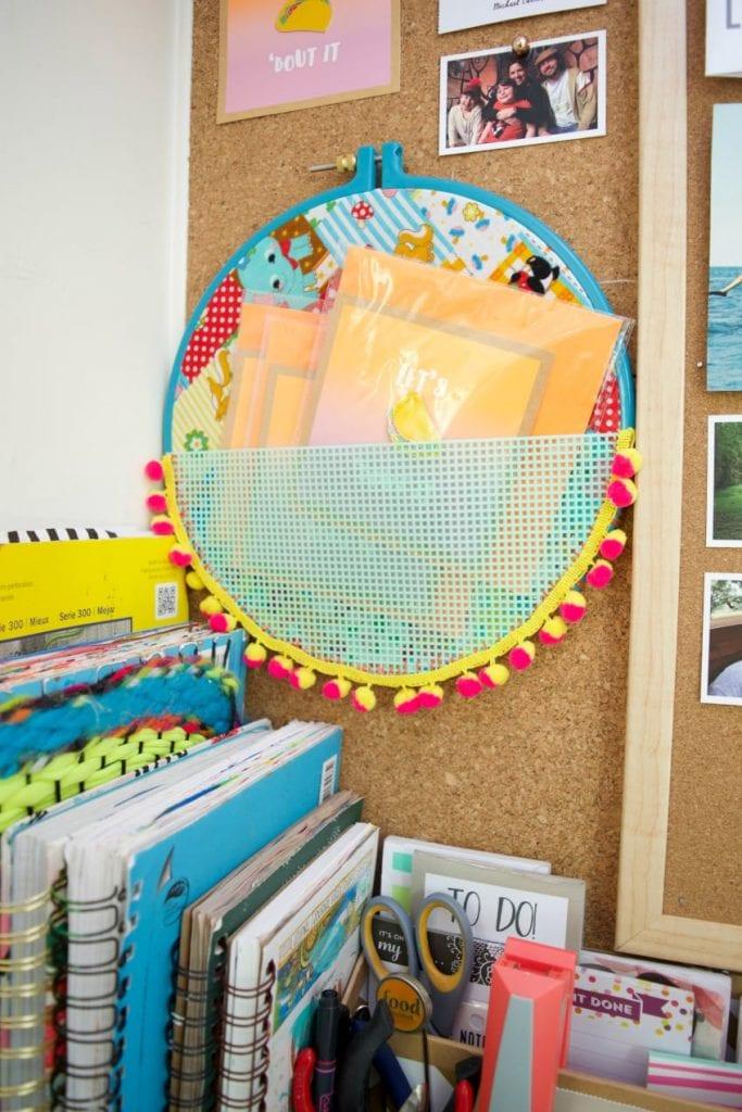 Embroidery hoop pocket organizer hanging on a desk.