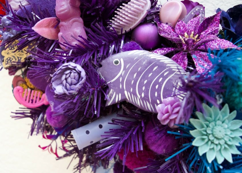 Close up of purple fish earring, roller and barbie brush.