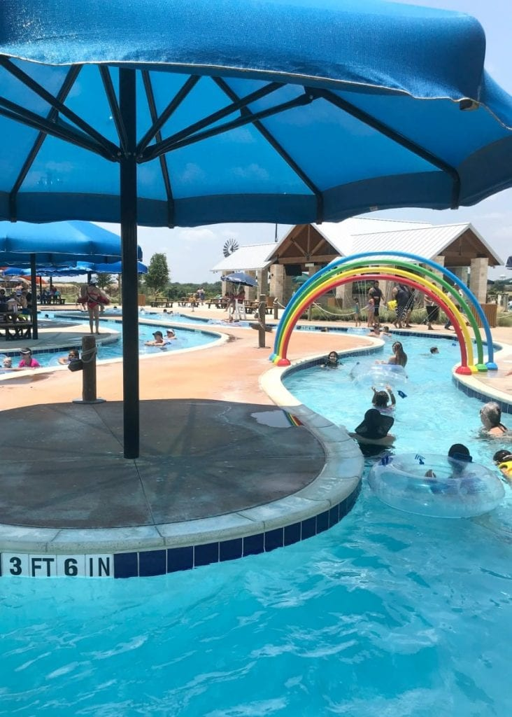 Rainbow water feature and lazy river with umbrellas.