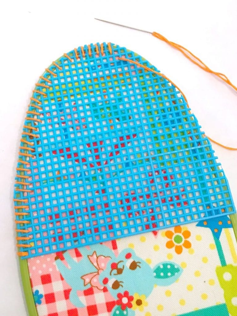 Stitch plastic canvas onto embroidery hoop with fabric to attach pocket.